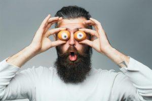 Bärtiger Mann hält sich zwei Eier vor die Augen