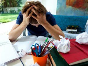 Verzweifelter Schüler über Schulbüchern