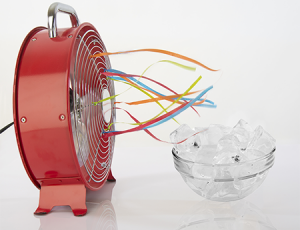 Roter Ventilator steht auf dem Boden, vor ihm steht eine Schüssel mit Eis.