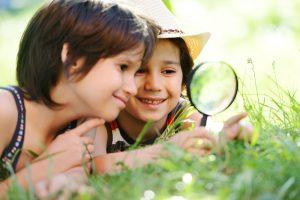 Kinder forschen mit einer Lupe im Gras