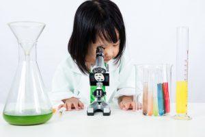 Junges Mädchen schaut, gekleidet in einem weißen Kittel, in eine Mikroskop.