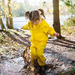 Kind springt in eine Matschpfütze