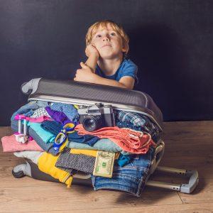 Junger vor gepacktem Koffer