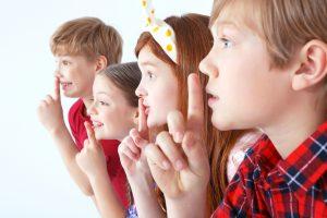 Kinder halten sich die Finger auf den Mund