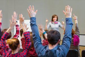 Schüler_innen heben ihre Hände nach oben