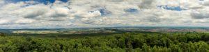 Ein Panorama von Winterstein, Hessen. Zu sehen ist ein grünes Baumkronenmeer und strahlend blauer Himmel mit Wolken.