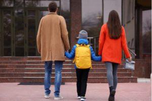 Eltern laufen mit ihrem Sohn ins Schulgebäude