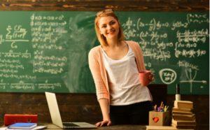 Lehrerin an ihrem Pult mit Laptop
