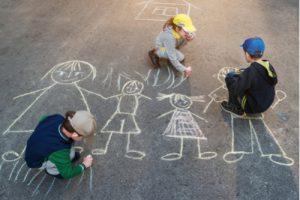 Kinder malen Familie mit Kreide auf Straße