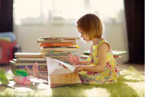 Mädchen blättert in einem Kinderbuch