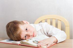 kleiner Junge alleine mit Bilderbuch