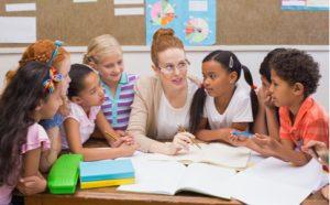 Lehrerin sitzt mit ihren Schülern am Tisch und erklärt etwas