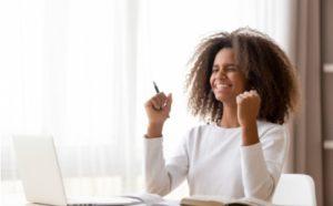 Mädchen sitzt vor ihren Hausaufgaben und freut sich