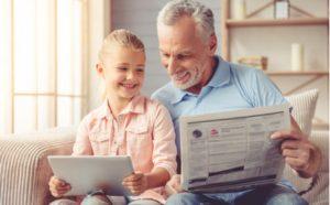 Vater und Tochter lernen mit Tablet und der Sprachzeitung Englisch