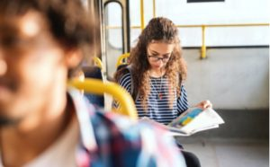 Mädchen liest eine Sprachzeitung im Bus