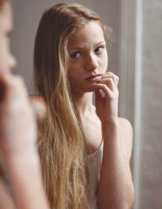 _Mädchen schaut sich im Spiegel an